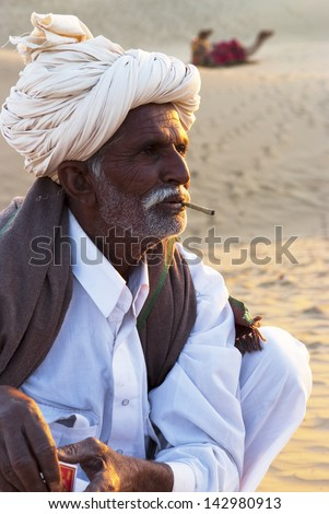 JAISALMER, INDIA-FEB 26: A cameleer waits for tourists at the Sam Sand Dune on Feb 26, 2013 in Jaisalmer, India.Apart from farming, camel riding activity is another income source for desert villagers - stock photo