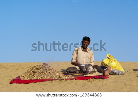 JAISALMER, INDIA - FEB 25:  A street vendor sells baked peanuts at the Sam Sand Dune on Feb 25, 2013 in Jaisalmer, India during the Desert Festival which is held in winter to attract tourists. - stock photo