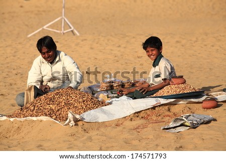 JAISALMER, INDIA - FEB 25: A street vendor with unidentified boy sells baked peanuts at the Sam Sand Dune on Feb 25, 2013 in Jaisalmer, India during the Desert Festival which is held in winter to attract tourists. - stock photo
