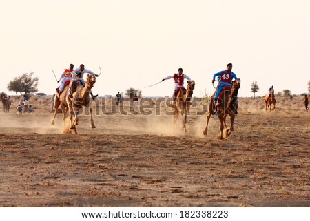 JAISALMER, INDIA - FEB 25: Camel racing on Feb 25, 2013 in Jaisalmer, India. The event is part of the Desert Festival held in winter to attract both domestic and international tourists. - stock photo