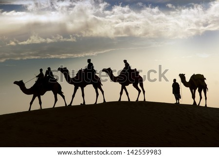 JAISALMER, INDIA - FEB 26:  Camel riding in Thar Desert, on Feb 26, 2013 in Jaisalmer, India.  Apart from farming, camel riding activity is another income source for desert villagers - stock photo