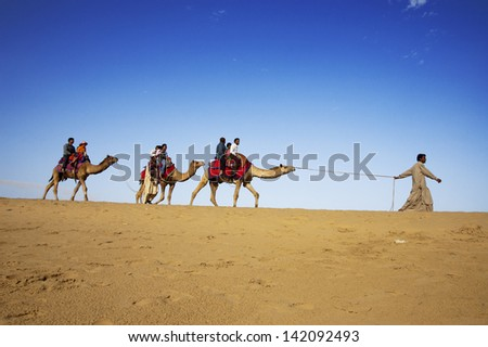 JAISALMER, INDIA - FEB 25:  Cameleer and customers at the Sam Sand Dune on Feb 25, 2013 in Jaisalmer, India.   Apart from farming, camel riding activity is another income source for desert villagers - stock photo