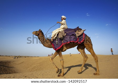 JAISALMER, INDIA - FEB 25: Cameleer waits for tourists at Sam Sand Dune on Feb 25, 2013 in Jaisalmer, India. Apart from farming, camel riding activity is another income source for desert villagers - stock photo