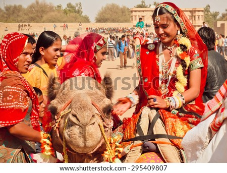 JAISALMER, INDIA - FEB 1: Happy faces of village women in red sari riding the camels during the rural Desert Festival on February 1, 2015. Every winter Jaisalmer takes the famous Desert Festival - stock photo