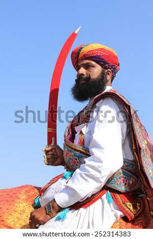 JAISALMER, INDIA - FEB 01: Traditionally dressed Rajasthani man holding sword rides on a camel during a cultural procession for Desert festival held on February 01, 2015 in Jaisalmer, Rajasthan, India. - stock photo