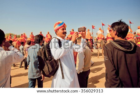 JAISALMER, INDIA - FEB 1: Two indian men making photo portraits with mobile phone during the Desert Festival on February 1, 2015 in Rajasthan. Every winter Jaisalmer takes the Desert Festival - stock photo