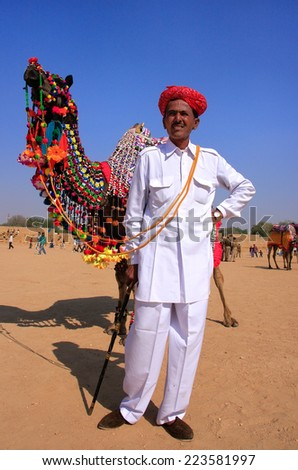 JAISALMER, INDIA - FEBRUARY 16: Unidentified man leads camel during Desert Festival on February 16, 2011 in Jaisalmer, India. Main purpose of Festival is to display colorful culture of Rajasthan. - stock photo