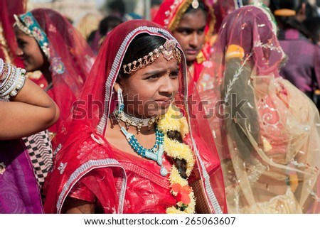 JAISALMER, INDIA - MAR 1: Cute woman looking the friends in the crowd of indian ladies during the Desert Festival on March 1, 2015. Every winter Jaisalmer takes Desert Festival of Rajasthan - stock photo