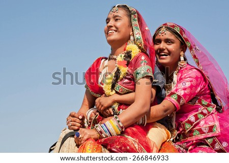 JAISALMER, INDIA - MAR 1: Happy faces of village women in red dresses drive the camel during the rural Desert Festival on March 1, 2015. Every winter Jaisalmer takes the famous Desert Festival - stock photo