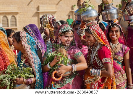 JAISALMER, INDIA - MAR 1: Happy young women dressed in traditional indian sari walking on the famous Desert Festival on March 1, 2015. Every winter Jaisalmer takes the Desert Festival of Rajasthan - stock photo