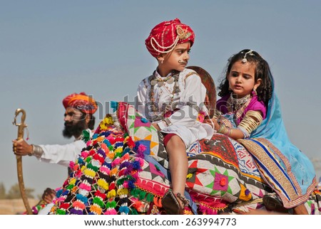 JAISALMER, INDIA - MAR 1: Unidentified boy and girl like a royal family sitting on the camel back and drive to the Desert Festival on March 1 2015. Every winter Jaisalmer takes famous Desert Festival - stock photo