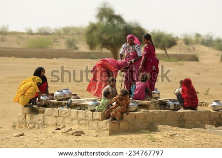 JAISALMER,INDIA - November 9,2014 : Unidentified women draw water form the well and take it to their home in rural ares of Jaisalmer,India. - stock photo