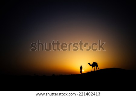JAISALMER - MARCH 22 : man with camel posing in the desert on March 22 , 2014 in Jaisalmer,India  - stock photo