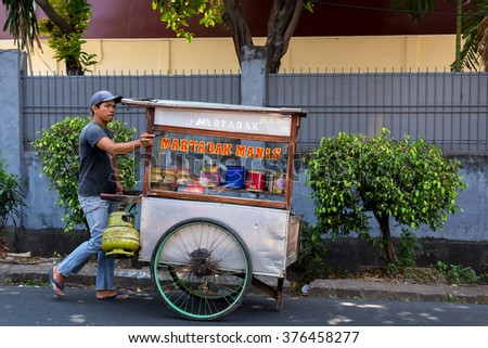 JAKARTA - August 10: Indonesian man sells local fast food in a movable barrow vehicle. August 10, 2015 in Jakarta, Indonesia. - stock photo