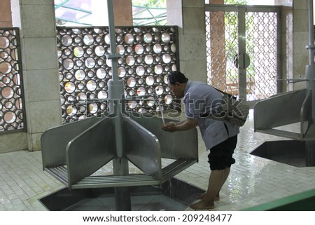 """JAKARTA, INDONESIA-APR. 6:  A Muslim performs required cleansing at the Istiqlal Mosque prior to attending prayer service on April 6, 2014 as Muhammad said """"Cleanliness is half of faith"""".   - stock photo"""