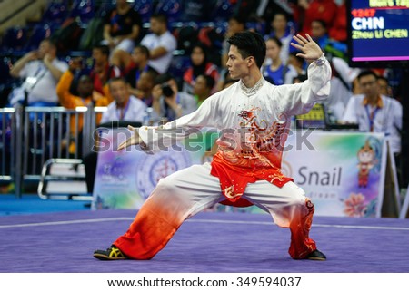 JAKARTA, INDONESIA - NOVEMBER 15, 2015: Zhou Li Chen of China performs the movements in the men's Taijiquan event at the 13th World Wushu Championship 2015 held in Istora Senayan, Jakarta. - stock photo