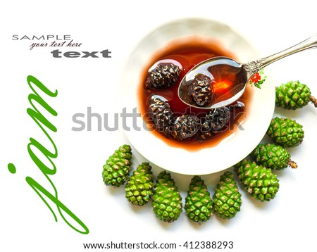 Jam from cones in a white plate and green cones on white table - stock photo