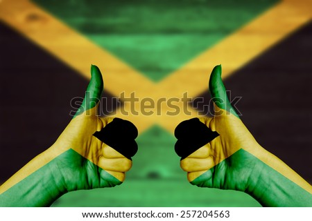 Jamaica flag painted on female hands thumbs up with blurry wooden background - stock photo