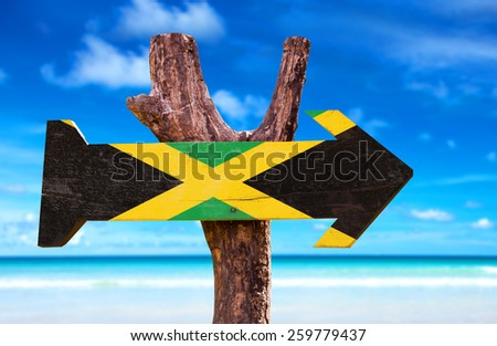 Jamaica Flag sign with beach background  - stock photo