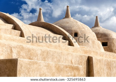Jami al-Hamoda Mosque located in the town of Jalan Bani Bu Ali, Sultanate of Oman with its unique structure of 52 domes and a falaj used for ablutions running through the courtyard. - stock photo