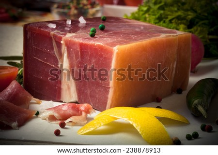 jamon piece lying on the table with spices - stock photo