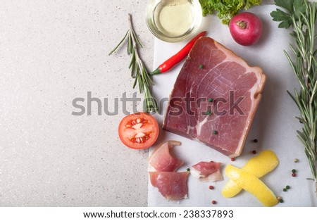 jamon piece lying on the table with spices.tinted - stock photo