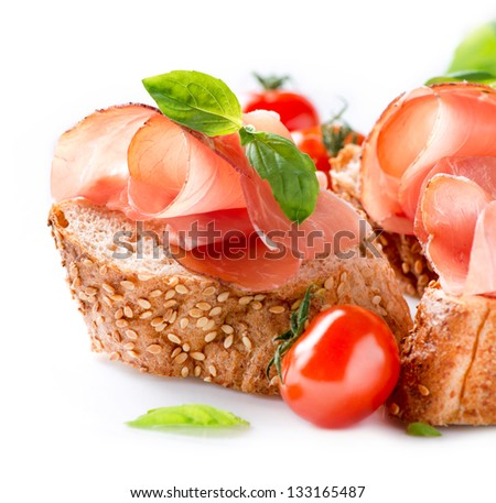 Jamon. Slices of Bread with Spanish Serrano Ham Served as Tapas. Cured ham, spanish appetizer. Prosciutto isolated on white background - stock photo