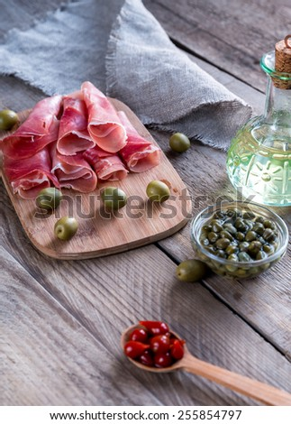 Jamon with capers and olives on the wooden board - stock photo