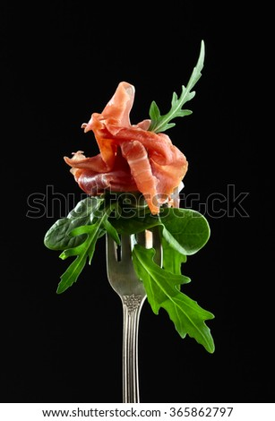 jamon with spinach and  arugula on dark background - stock photo