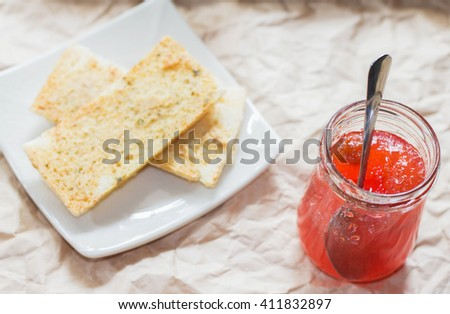 Jams and biscuits on a plate, put a wooden table. - stock photo