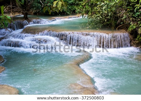 Jangle landscape with amazing turquoise water of Kuang Si cascade waterfall at deep tropical rain forest. Luang Prabang, Laos travel landscape and destinations - stock photo