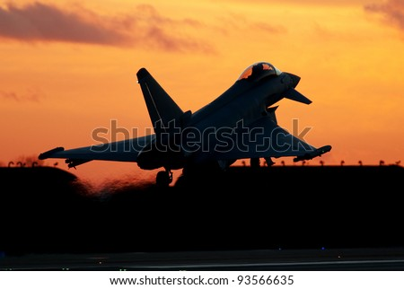 January 2012. Eurofighter Typhoon supersonic fighter aircraft unmarked but flying with No 29[R] Squadron. RAF Coningsby, Lincolnshire, UK. Seen landing at sunset. Silhouette. - stock photo