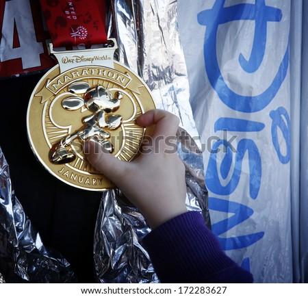 January 12, 2014, Walt Disney World Marathon: Child holding Walt Disney Marathon gold medal with running Mickey Mouse - stock photo
