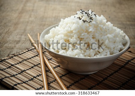 Japan rice and black sesame seeds with chopsticks on a bamboo mat - stock photo