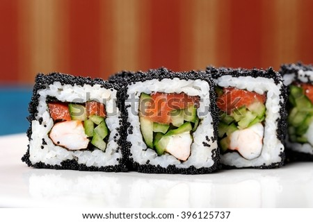 Japan square black tobiko rolls with shrimp, salmon and cucumber copyspace copyspace - stock photo