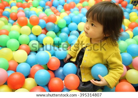 Japanese baby girl playing in ball pool (1 year old) - stock photo