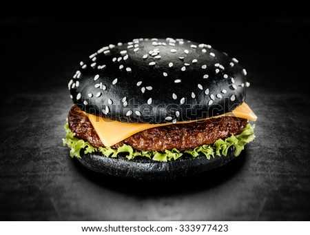 Japanese Black Burger with Cheese. Cheeseburger from Japan with black bun on dark background - stock photo