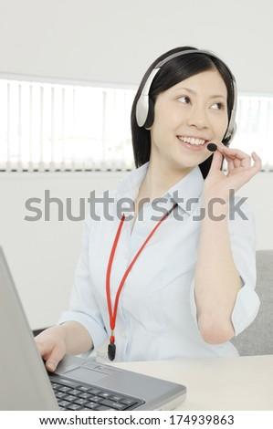 Japanese business Woman talking on headset - stock photo