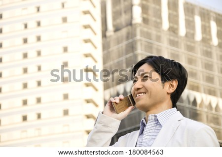 Japanese businessman using mobile phone - stock photo