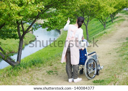 Japanese caregivers and senior in the field - stock photo