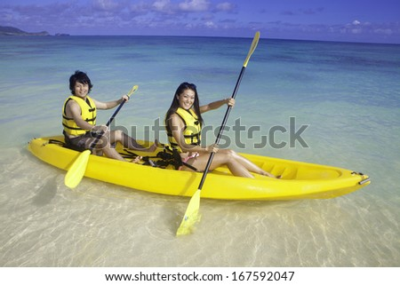 japanese couple kayaking in hawaii - stock photo