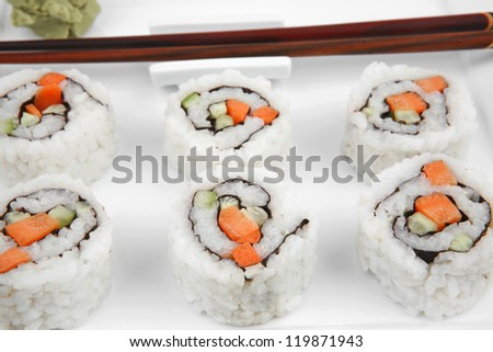 Japanese Cuisine - California Roll with Cucumber , Cream Cheese and Raw Salmon inside. Served with wasabi . Isolated over white background on square plate - stock photo