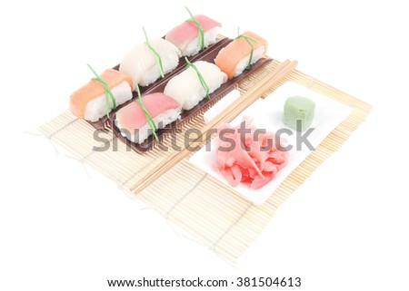 Japanese Cuisine - Different Types of Nigiri Sushi Tuna (maguro) Salmon (sake) and Eel (unagi) with Wasabi and Ginger on bamboo mat isolated over white background - stock photo