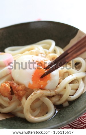 japanese cuisine, hot spring poached egg with kamaboko on udon noodle - stock photo