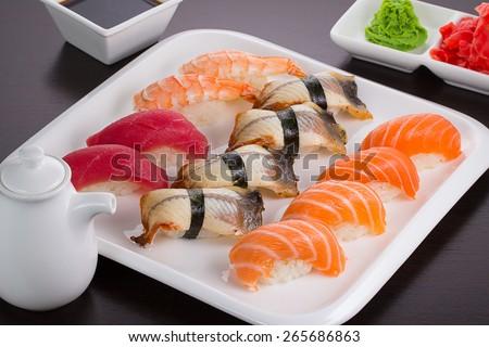 Japanese cuisine. Set of sushi nigiri on white plate. - stock photo