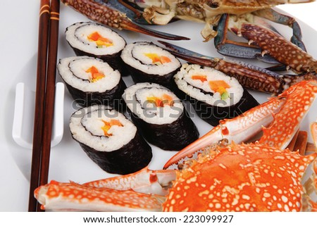 Japanese Cuisine : Sushi Maki Roll with Vegetables and Salmon inside . on black dish with red and blue crabs . - stock photo