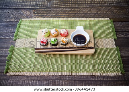 japanese cuisine. sushi on mat and wood background, vintage. - stock photo
