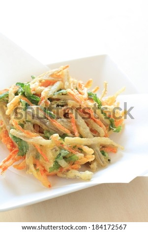 Japanese dish of shredded vegetables coated in batter and fried. - stock photo