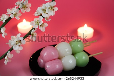 Japanese dumpling with Ume (Japanese plum) blossoms and candles - stock photo