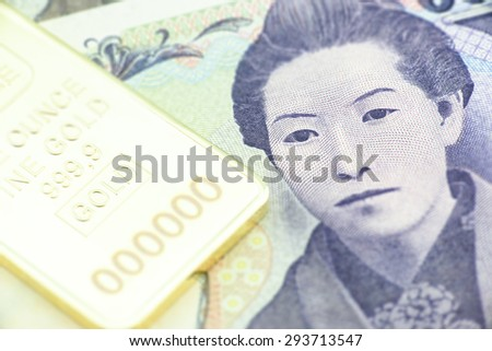 Japanese five thousand yen bill, a macro close-up with gold bullion - stock photo